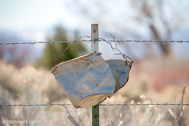 bucket hanging on a fence post