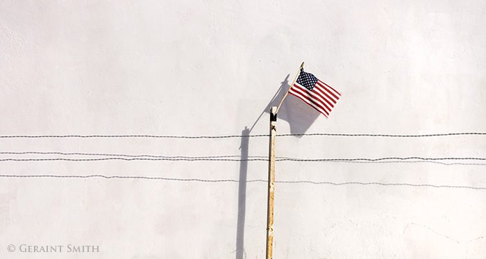 usa flag on a post, white wall, wire fence