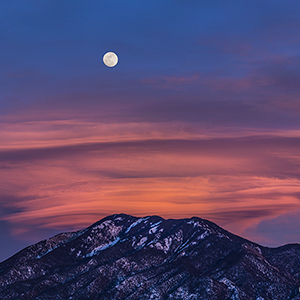 "The ""Snow"" Moon and lenticular clouds over Taos Mountain."
