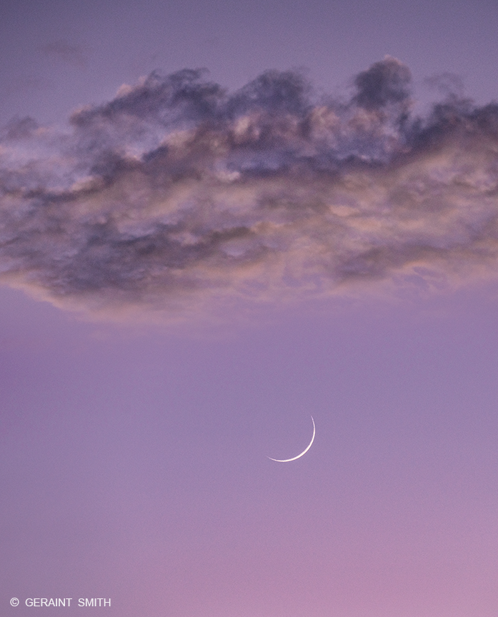 Crescent moon and cloud in a mauve sky.