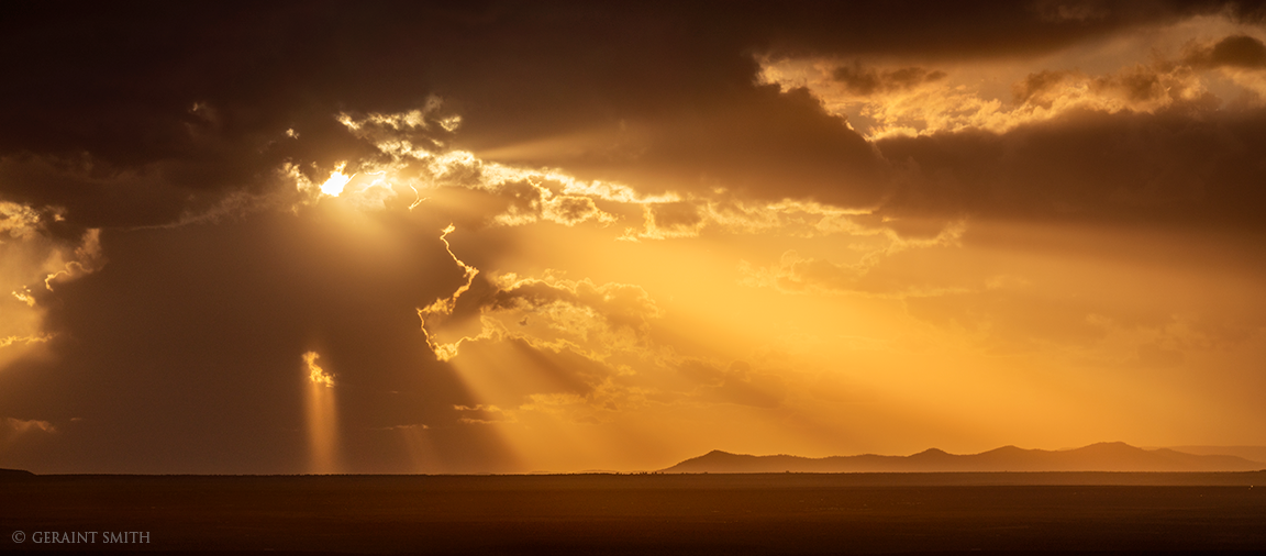 Taos Plateau, sunset rays with storm clouds brewing.